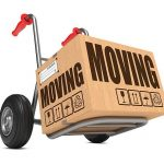 Moving - Slogan on Cardboard Box on Hand Truck White Background.