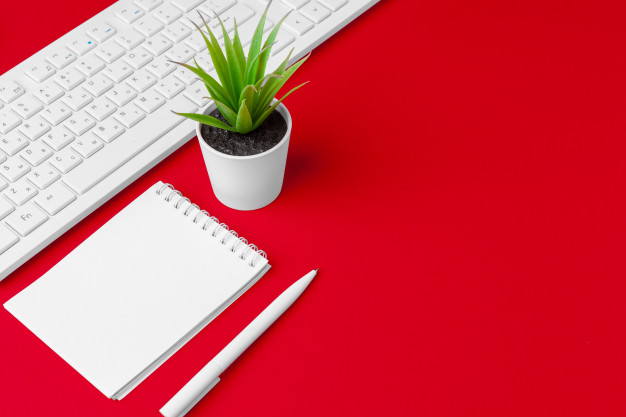 red-office-desk-table-with-blank-notebook-keyboard-supplies-top-view-with-copy-space-flat-lay_93675-62358